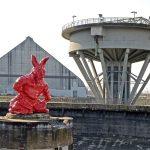 """Der """"Rote Hase"""" von Thomas Schütte auf dem ehemaligen Zechengelände erweckt bei den Besucher Ratlosigkeit und mitunter Verärgerung. Im Hintergrund steht die riesige Kohlenmischhalle, der Premieren-Ort der Ruhrtriennale 2015."""