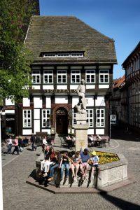 Der Eulenspiegel-Brunnen stammt aus dem Jahr 1942 und liegt optisch dominierend in der Mitte des Einbecker Marktplatzes vor der Marktkirche, flankiert von Rathaus, Brodhaus und Ratsapotheke. Benannt ist er nach Till Eulenspiegel, einem früheren Gast. – Foto: Stadt Einbeck