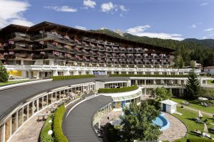 Außenfassade mit Blumenschmuck. - Foto: Krumers Alpin Resort & SPA