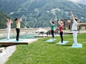 Schwungvoll in den Tag mit Yoga – und mit einer grandiosen Aussicht ins wunderschöne Tal mit dem idyllischen Ort. Foto: Schultz Gruppe