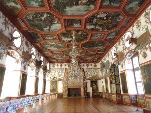 : Der Rittersaal von Schloss Weikersheim, entstanden um 1600, ist überwältigend reich ausgestattet. Trotz der riesigen Dimension von 40 Metern Länge kommt seine weite hölzerne Decke ohne Stützen aus. Sie hängt am Dachstuhl – ein technisches Meisterwerk.