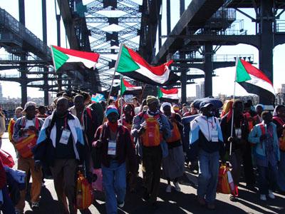 Sudanesische Pilger tanzen und singen auf der Harbour Bridge.