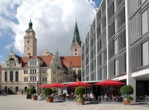 """Alt und neu verbinden sich am Rathausplatz, wo das Alte Rathaus (Mitte) und das Neue Rathaus (rechts) einen Gegenpol bilden, wie er auffälliger nicht sein könnte. Hinten links der Pfeifturm, rechts die """"Untere Pfarr"""" (Moritzkirche)."""