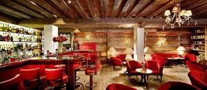 Die American Bar ist großzügig gestaltet; samtrote Fauteuils, Holzkamin und Kachelofen sorgen für eine heimelige Atmospäre.