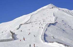 Beinahe kitschig, wie ein Gemälde, schaut der Gipfel des Speierecks aus; darunter tummeln sich viele Skifahrer. - Foto: Goldeck-Speiereck