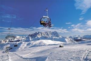 Mit dem Vierer-Sessel geht es hinauf auf die Alpe Lusia. Dort erwarten den Skifahrer traumhafte Pisten und ebensolche Ausblicke. – Foto: Luis Kostner