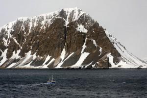Fischerboot vor Bergmassiv.