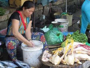 Fisch-, Fleisch- und Gemüsemarkt. Auf dem Markt wird das Huhn in kleinste Einzelteile zerlegt und auf geflochtenen Schüsseln in Bodennähe angeboten.