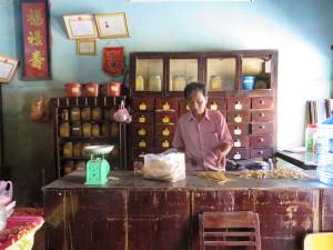 Der Apotheker zerteilt Ginseng und bereitet es zum Verkauf vor. Seine Apotheke steht in Hoi An, dessen Altstadt die letzten zweihundert Jahre unverändert überdauert hat und zum UNESCO-Weltkulturerbe gehört.