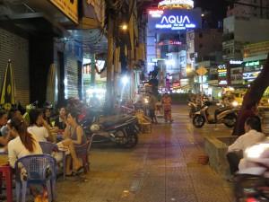 Saigon bei Nacht: Endlich einmal begehbar, der Fußgängerweg zwischen parkenden Rollern, den Garküchen am Straßenrand und ihren Gästen.