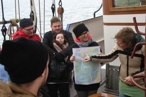 Rita erklärt auf der Seekarte den Kurs für die Rückfahrt.