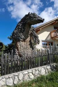 Ein mächtiger Zeitgenosse ist der Ursus Ladinicus. Dieses Kunstwerk aus Holz ist in Oies, dem Geburtsort von Josef Freinademetz, anzutreffen. – Foto: Dieter Warnick