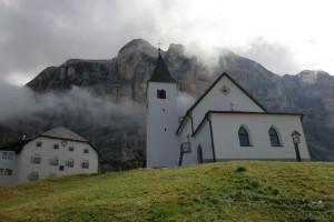 Der Heiligkreuzkofel begrenzt das Gadertal ostseitig. Unterhalb der Westwand liegen die Wallfahrtskirche Heiligkreuz (rechts) und das Schutzhaus Heligkreuz-Hospiz (links). – Foto: Dieter Warnick