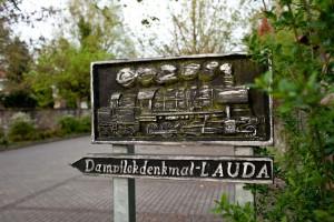 Das Dampflokdenkmal  – hier ein Hinweisschild – ist zu einem Wahrzeichen der Stadt Lauda-Königshofen geworden. – Foto: Touristik-Information Lauda-Königshofen