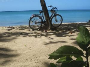 Sonne, Strand und blaue See, eine Bilderbuch-Vorstellung von der Karibik. Ungewöhnlich das Rad. Es half bei der Entdeckung der vielen Inseln der Kleinen Antillen.