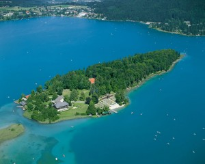 Die Insel im Faaker See ist ein Naturidyll und ein einzigartiger Ort zum Abschalten vom Alltag  – ob für einen Badetag, ein genüssliches Abendessen im Insel-Restaurant oder für einen entspannten Urlaub mitten im See. – Foto: Region Villach