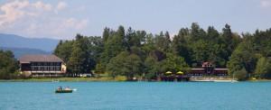 Das Inselhotel im Faaker See ist ein romantisches 4-Sterne Hotel mit einladendem Seerestaurant (links). Rechts das historische, denkmalgeschützte Badehaus aus dem Jahr 1929. – Foto: Region Villach