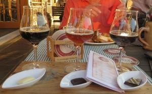 Drei von sehr vielen verschiedenen Biersorten von Camba Bavaria mit jeweils einem anderen Stück Lindt-Schokolade, das den Geschmack des Bieres verfeinert.