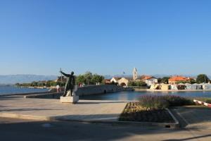 Die auf einer künstlich geschaffenen Insel liegende Altstadt von Nin ist durch zwei Brücken (eine davon hier im Bild) mit dem Festland verbunden. Die Statue zeigt den Fürsten Branimir, den ersten gesetzlichen Herrscher eines unabhängigen kroatischen Staates.