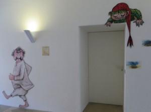 Ob außen oder innen im Kloster Seeon, überall begleiten den Besucher die Figuren aus Preußlers Kinderbüchern. Hier beobachtet der kleine Wassermann, wer aus der Toilette kommt.