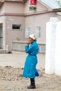 Eine Frau in Gachuurt wartet an der Bushaltestelle.