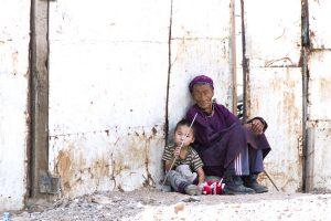 Großmutter und Kind sitzen und warten im armen Viertel Ulan Bators.