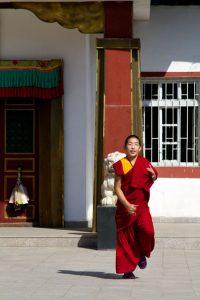 Ein junger Mönch läuft enthusiastisch aus dem Pethub Kloster nach dem morgendlichen Gebet.
