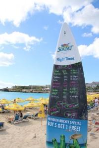 Maho Beach: Ein in den Sand eingelassenes Surfbrett dient als Tafel und zeigt die nächsten Landeanflüge an, denn hier wollen alle Gäste das gleiche: Das Super-Selfie mit Düsenjet!