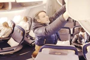 Interessante Perspektiven: Der Betrachter sieht die Szene aus einem Gepäckfach. Foto: Lufthansa