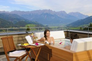 Romantiker können Arrangements für private Stunden in der Panorama-Badewanne auf dem Dach buchen. - Foto: Holzhotel Forsthofalm