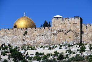 In Jerusalem wird die imposante Tempelmauer unterbrochen durch das Goldene Tor, durch das der Messias, wie die Juden glaubten, die Stadt betrete. Deshalb und aus strategischen Überlegungen vermauerten die Araber das Tor und legten einen Friedhof davor an. Links neben dem Tor die vergoldete Aluminium-Kuppel des Felsendoms.