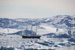 Dieser Dreimaster wirkt zwischen den gigantischen Eisbergen ziemlich klein.