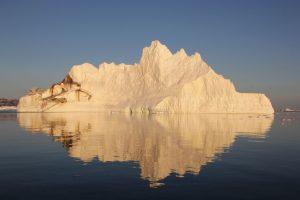 Eisberg spiegelt sich im kristallklaren Wasser.