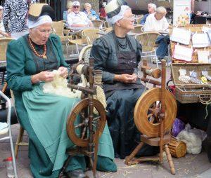 Auf dem Markt in Schagen versammeln sich jeden Donnerstag in den Sommermonaten viele Frauen und Männer in den traditionellen Trachten Nordhollands und veranschaulichen, wie es vor hundert Jahren war. Hier zeigen zwei Frauen, wie gesponnen wird.