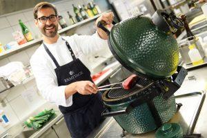 """Der Küchenchef bereitet Fleisch im Big Green Egg zu. Eine von der NASA ursprünglich fürs Raumfahrtprogramm entwickelte Keramiktechnologie sorgt für enorme Hitze und höchst gleichmässige Temperaturverteilung im """"Ei"""", was das Fleisch später auf der Zunge schmelzen lässt. Foto: Ermitage Wellness & Spa Hotel"""