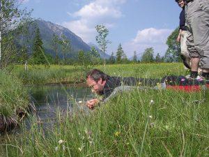 Ein interessierter Urlauber betrachtet aufmerksam eine Ammerquelle bei Oberammergau. - Foto: Ammergauer Alpen / Thomas Bichler