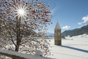 Der Turm im Reschensee/Vinschgau kurz hinter der österreichisch-italienischen Grenze markiert die Verbindung zwischen Nord- und Südtirol. - Foto: Vinschgau Marketing/Frieder Blickle