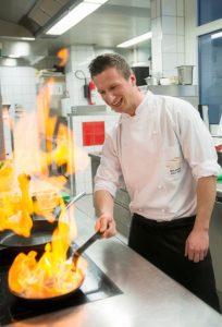 Spaß am Kochen - Chefkoch Maximilian Moser beim Flambieren in der Küche.
