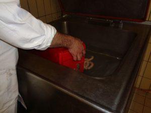 """Uli Hofhherr gibt die fertigen """"Weißen"""" in 70 Grad heißes Wasser; dort ziehen sie etwa 20 Minuten und stehen dann zum Verzeht bereit. - Foto: Dieter Warnick"""