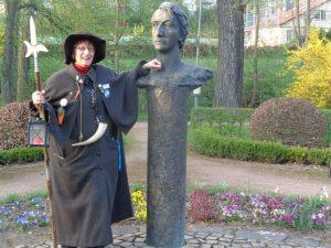 : Heiligenstadts Nachwächterin Heidelinde Liepe steht neben dem Denkmal von Heinrich Heine, das im Kurpark seinen Platz gefunden hat. Der Dichter (1797 – 1856) ließ sich in Heiligenstadt taufen. Er wählte diesen Ort, weil er die Taufe geheim halten wollte. – Foto: Dieter Warnick