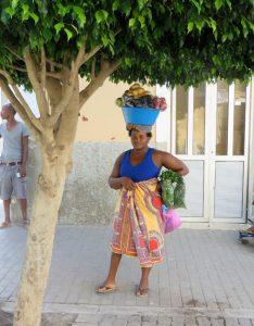 Kess und unbefangen, trotz der schweren Last auf dem Kopf, beäugt sie uns und wundert sich, dass Weiße bei dieser Hitze mit dem Rad durch Praya, der Hauptstadt des afrikanischen Inselstaates Cabo Verde, fahren.
