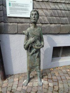 """""""Der junge Schafhirte"""" in der Weststraße von Schmallenberg soll an das Mittelalter erinnern, in dem die Stadt durch das von den Einwohnern betriebene Wollgewerbe Bedeutung erlangt hatte. Zahlreiche Handwerke lebten in und um Schmallenberg von der Herstellung und Verarbeitung von Wolle und Tüchern, und das bis in die heutige Zeit. Das in Schmallenberg ansässige Familienunternehmen """"Falke"""" stellt vor allem hochwertige Strumpf- und Stickwaren her. Insgesamt beschäftigt die Falke-Gruppe 3200 Mitarbeiter im In- und Ausland. – Foto: Dieter Warnick"""