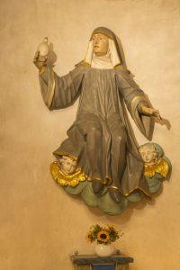 In der Wormbach Pfarrkirche befindet sich eine Figur der Heiligen Walburga in der Apsis des rechten Seitenschiffes. Als Emblem trägt sie in der rechten Hand eine Ampulle. – Foto: Schmallenberger Sauerland Tourismus / Klaus-Peter Kappest