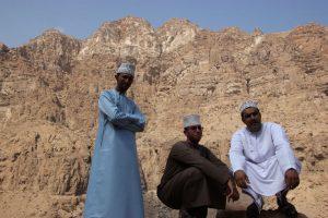 Omanis vor einer imposanten Felskulisse. - Foto: Michael Stephan