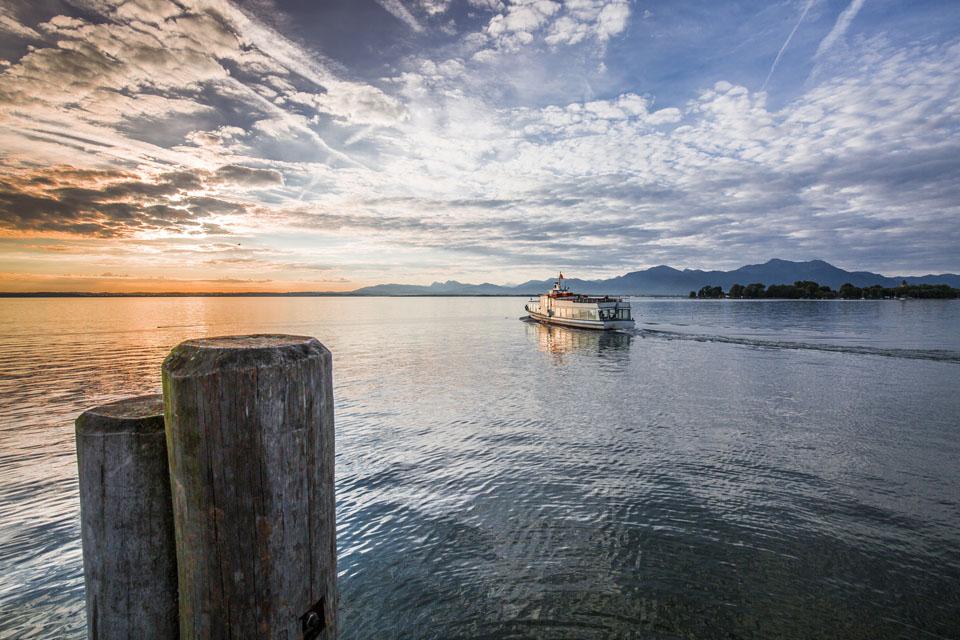 Abendstimmung am Chiemsee. Ein Ausflugsboot macht sich auf zu seiner letzten Fahrt an diesem herrlichen Tag. - Foto: Chiemsee-Alpenland Tourismus