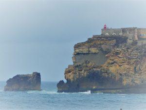 Die Felsenspitze mit dem Leuchtturm, Farol da Nazaré, ragt weit in das Meer und teilt den Strand in einen südlichen und nördlichen Teil.