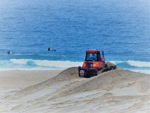 Große Planierraupen schieben den angespülten Sand ins Meer zurück.