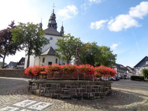 Hallenberg ist die kleinste westfälische Gemeinde sowie die zweitkleinste Stadt von Nordrhein-Westfalen. Am Südrand des Marktplatzes des historischen Fachwerkstädtchen bildet der Petrusbrunnen einen optischen Kontrapunkt zur St.-Heribert-Kirche, deren Entstehung ins 13. Jahrhundert zurückreicht. – Foto: Dieter Warnick