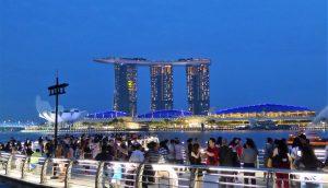 Am Singapore River vor den drei 55-stöckigen Hoteltürmen von Marina Bay Sands, die einen 340 Meter langen Dachgarten samt Pool tragen. Daneben befindet sich das Art-Science Museum in Form einer Lotusblüte.