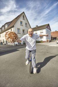 Sportlich, sportlich, und Bäcker mit Leib und Seele: Arnd Erbel balanciert auf dem Einrad einen Laib Bauernbrot. - Foto: www.bayern.by / Gert Krautbauer